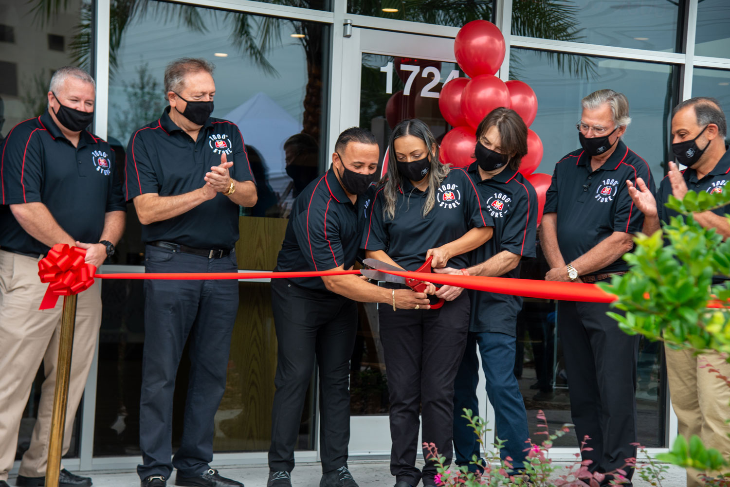 Cutting the ribbon at the grand opening of the 1000th Marco's Pizza location.